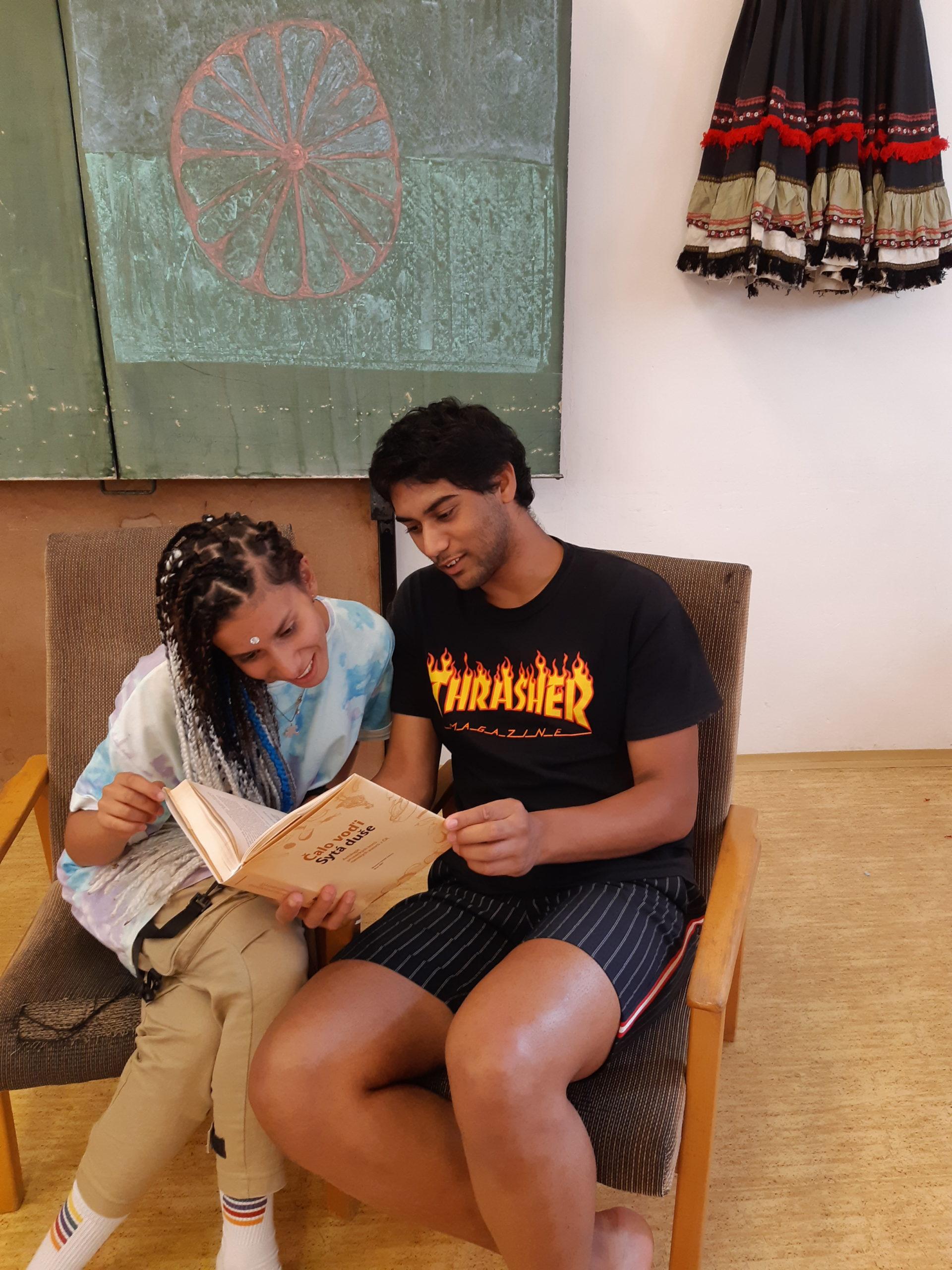 Romský chlapec a romská dívka si společně čtou v knize romských autorů Čalo voďi.